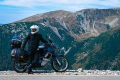 Motorcyklistman och affärsföretagmoped på överkanten av berget Motorcykeltur Värld som reser, livsstilloppsemestrar arkivbilder
