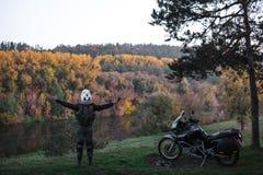 Motorcyklistmannen st?r med hans utstr?ckta armar Aff?rsf?retagmotorcykeln, motorcyklistkugghjul, en mopedchauff?r ser, begreppet royaltyfri bild