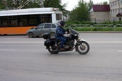 Motorcyklistridning på hans motorcykel på solnedgången Royaltyfria Foton