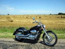 Motorcyle dichtbij hooigebied Stock Foto