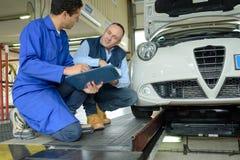 Motore della correzione di Helping Apprentice To del meccanico Fotografie Stock