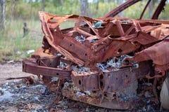 Motore fuori bruciato di un relitto arrugginito dell'automobile Fotografia Stock