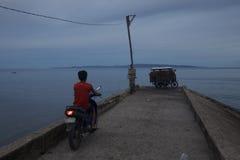 Motore-motociclista sul pilastro al tramonto Immagine Stock