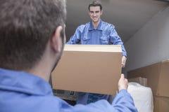 Motores que descargan una furgoneta móvil, pasando una caja de cartón Foto de archivo libre de regalías