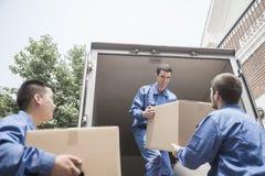Motores que descargan una furgoneta móvil, pasando una caja de cartón Imagen de archivo libre de regalías