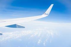 motorförbundet com brännmärker på flygplanvingen ovanför molnet och mot blå himmel Royaltyfri Bild