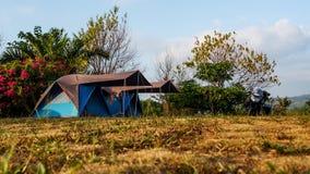 Motorfiets op bruin gras naast tent, beschikbare ruimte wordt geparkeerd die camping royalty-vrije stock foto's