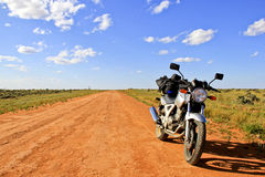 Motorfiets op een leeg landwegBinnenland Australië Royalty-vrije Stock Afbeeldingen