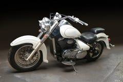 Motorfiets tegen donkere achtergrond stock afbeeldingen