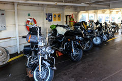 Motorfietsen in een veerboot op een zonnige dag worden opgesteld die Stock Foto