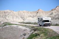 Motorhem RV som reser in i badlandsna nationalpark, South Dakota fotografering för bildbyråer