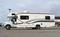 Motorhome 3. A motor home in a parking lot with some location background in the distance. Side view Stock Photography