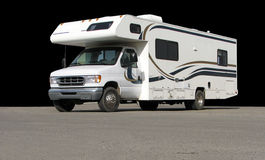 Motorhome. White Recreational vehicle on pavement against a black background Stock Images