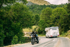 Motorhome car and rider on bike moving along a mountain road on Stock Images