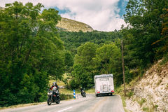 Motorhome car and rider on bike moving along a mountain road Royalty Free Stock Image