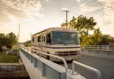 A motorhome drives across a bridge at dusk. A motorhome drives across a small, two lane bridge at dusk royalty free stock photography
