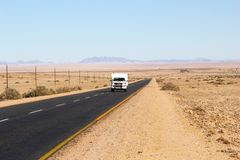 Motorhome driving B4 highway Aus Luderitz, Namibia. Motorhome is driving on the B4 highway through the desert from Aus to Luderitz in Nambia Royalty Free Stock Images