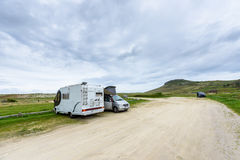 Motorhome RV and campervan are parked on a beach. Royalty Free Stock Image
