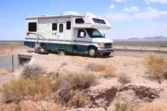 Motorhome RV with Flat in Desert. RV Motorhome on the side of a desert road, with the driver fixing a flat tire Stock Photography