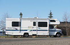 Motorhome Sideview. A side view of a white motor home in a parking lot with trees, blue sky and a couple of distant buildings in the background. Bike on carrier Royalty Free Stock Photos