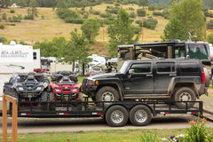 A motorhome towing atvs and a hummer Stock Images