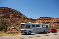 A motorhome towing a car through the desert. An rv driving through colorful sandstone cliffs in utah`s wilderness Royalty Free Stock Images