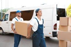 Motori maschii che scaricano le scatole dal furgone fotografia stock