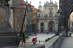Motorini rossi di spinta contro il contesto della chiesa di StSalvator a Praga, repubblica Ceca fotografia stock
