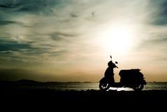 Motorino della siluetta alla spiaggia Fotografie Stock