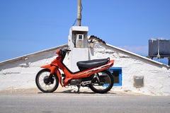 Motorino parcheggiato davanti alla vecchia casa di pietra Fotografia Stock Libera da Diritti