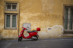 Motorino rosso luminoso della vespa in una via urbana Immagine Stock Libera da Diritti