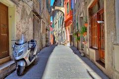 Motorino sulla via stretta in Ventimiglia, Italia. immagini stock libere da diritti