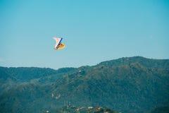 Motoriserade Hang Glider Flying Over Mountain kullar i blått fri Sunny Sky Royaltyfri Bild