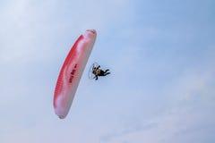 Motoriserat paragliderflyg i den blåa himlen Arkivfoto