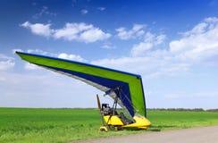 Motorisiertes Bedeutungssegelflugzeug über grünem Gras Lizenzfreie Stockfotos