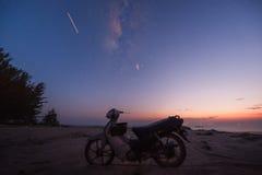 Motorisk cykel på stranden under skymning Arkivbilder