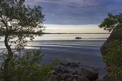 Motoriskt fartyg med två fiskare på golfen av Finland på bakgrunden av en färgrik solnedgång Royaltyfria Bilder