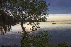 Motoriskt fartyg med två fiskare på golfen av Finland på bakgrunden av en färgrik solnedgång Arkivbild
