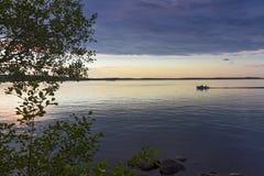 Motoriskt fartyg med två fiskare på golfen av Finland på bakgrunden av en färgrik solnedgång Royaltyfri Fotografi