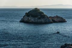 Motoriskt fartyg in mot den lilla ön i det blåa Ionian havet royaltyfria bilder