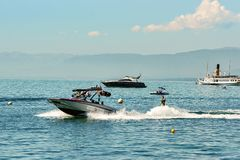 Motoriskt fartyg och man som wakeboarding i sjöGenève i Lausanne Royaltyfri Bild