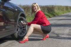 Motorist checking tire pressure of a car Stock Images
