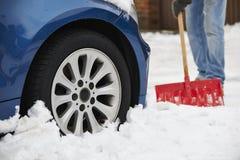 Motorist Digging Car Out Of Snow Stock Photos