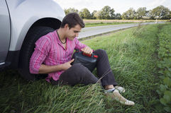 Motorist with empty petrol can. Young man sat at side of road by car with empty petrol can Royalty Free Stock Photography