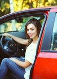 Motorista bonito da jovem mulher atrás do carro do vermelho da roda Imagens de Stock