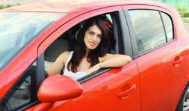 Motorista bonito da mulher atrás do carro do vermelho da roda Foto de Stock Royalty Free