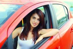 Motorista bonito da mulher atrás do carro do vermelho da roda Imagens de Stock