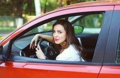 Motorista bonito novo da mulher atrás do carro do vermelho da roda fotografia de stock royalty free