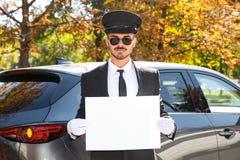 Motorista considerável novo com cartaz vazio perto do carro fotografia de stock