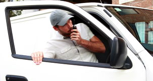 Motorista da entrega que fala no Walkietalkie e que obtém na camionete filme